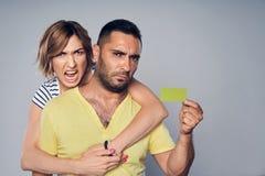 Carte fâchée de crédit en blanc d'apparence de couples de mécontentement photo stock