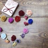 carte 14 février vacances Le boîte-cadeau et les roses se sont dedans étendus dans la forme de coeur sur la table en bois flatlay Image stock