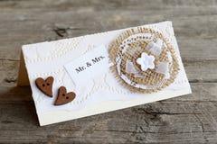 Carte faite main d'invitation de mariage décorée de la fleur de dentelle et de toile de jute et des coeurs en bois closeup Photo stock