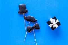 Carte felici di giorno del ` s del padre Smoking, baffi e biscotti e regalo del cappello Copyspace blu di vista superiore del fon Immagine Stock Libera da Diritti