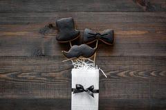 Carte felici di giorno del ` s del padre Smoking, baffi e biscotti e regalo del cappello modello di legno di vista superiore del  Fotografia Stock