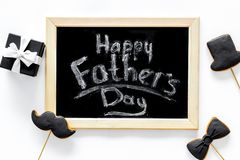 Carte felici di giorno del ` s del padre Smoking, baffi e biscotti e regalo del cappello Vista superiore del fondo bianco dello s Immagini Stock Libere da Diritti