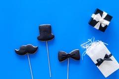 Carte felici di giorno del ` s del padre Smoking, baffi e biscotti e regalo del cappello Vista superiore del fondo blu Immagine Stock