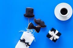 Carte felici di giorno del ` s del padre Smoking, baffi e biscotti e regalo del cappello Vista superiore del fondo blu Immagini Stock Libere da Diritti