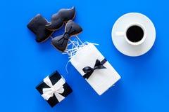 Carte felici di giorno del ` s del padre Smoking, baffi e biscotti e regalo del cappello Vista superiore del fondo blu Immagini Stock