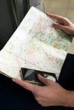 Carte géographique et un téléphone Vue de ci-avant Mains de la fille tenant une carte et un téléphone portable Image libre de droits