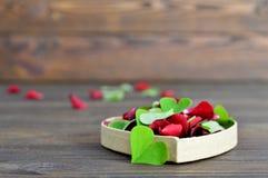 Carte heureuse de jour de valentines avec les feuilles en forme de coeur et les pétales de rose Image libre de droits