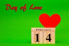 Carte heureuse de jour de valentines avec le coeur de papier rouge et le calendrier en bois Images libres de droits