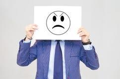 Carte hoding d'homme d'affaires avec le visage fâché d'isolement sur le gris image libre de droits