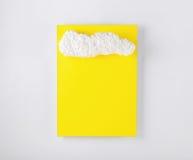 Carte jaune avec la mousse de styrol sous forme de nuages Photographie stock