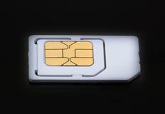 Carte mobile de sim sur le fond noir de plancher Photo libre de droits