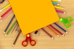 Carte orange s'étendant sur des crayons et des ciseaux de coloration Image stock