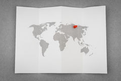 Carte pliée par papier du monde avec Pin Pointer rouge images stock