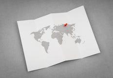Carte pliée par papier du monde avec Pin Pointer rouge photographie stock libre de droits