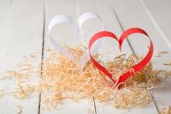 Carte postale au jour de Valentine Coeur blanc et rouge fait de bandes de papier Copeaux en bois bouclés décoratifs Photo libre de droits