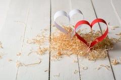 Carte postale au jour de Valentine Coeur blanc et rouge fait de bandes de papier Copeaux en bois bouclés décoratifs Photographie stock libre de droits