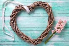 Carte postale avec la fleur rose et coeur décoratif sur le pai de turquoise Photo stock