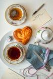 Carte postale avec le thé et le petit pain de bonbon sur la table blanche Images stock