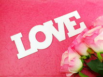 Carte postale avec les fleurs artificielles et étiquette avec des mots avec amour sur le fond rose Photographie stock