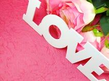Carte postale avec les fleurs artificielles et étiquette avec des mots avec amour sur le fond rose Photographie stock libre de droits