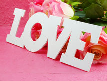 Carte postale avec les fleurs artificielles et étiquette avec des mots avec amour sur le fond rose Image stock