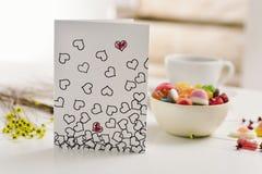 Carte postale avec quelques coeurs sur une table Image stock