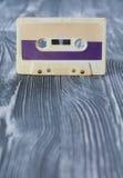 Carte postale de calibre de musique Cassette sonore violette sur le fond en bois gris photo stock