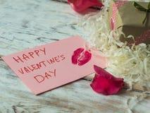 Carte postale de jour de valentines avec le cadeau et les pétales de rose sur le fond en bois Fin vers le haut Image stock