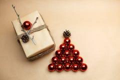 Carte postale de nouvelle année avec le cadeau au style d'eco et les arcs et les pinecones de rouge Photographie stock