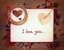 Carte postale du ` s de Valentine Tasse de café sur le livre ouvert avec le coeur en bois là-dessus Images libres de droits