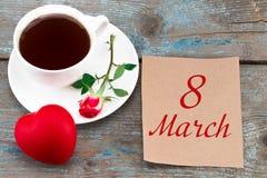 Carte postale 8 mars sur la table en bois avec du café, rose et le coeur Images stock