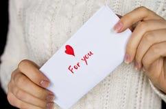 Carte postale pour le jour de valentines dans des mains de la fille Photos libres de droits