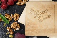 Carte postale romantique Une vue supérieure d'une carte mignonne, des coeurs de glace, des framboises roses et des noix sur un fo Photos stock