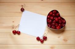 Carte pour des notes avec des cerises dans le boîte-cadeau de forme de coeur Image stock