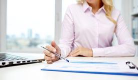Carte sorridenti della lettura della donna di affari in ufficio Fotografie Stock
