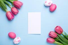 Carte, tulipes de fleurs et oeufs de pâques actuels sur un fond bleu image stock