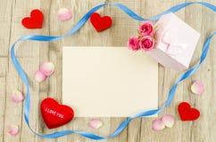 Carte vide avec la fleur, le boîte-cadeau, le coeur et le ruban roses Photographie stock libre de droits