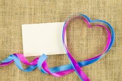 Carte vide avec le ruban en forme de coeur sur le fond de toile Photo libre de droits