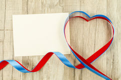Carte vide avec le ruban en forme de coeur sur le fond en bois Image libre de droits