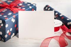 Carte vide de blanc de salutation Cadeau et matériaux d'emballage enveloppés au-dessus d'un fond en bois blanc Type de cru Photos libres de droits