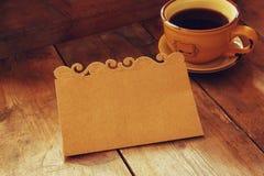 Carte vide de Brown au-dessus de fond de table et de tasse de café en bois rétros tons d'image de style, discrets et chauds Photographie stock libre de droits