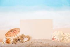 Carte vierge avec les coquilles de mer, coeurs en sable sur la plage Photos stock