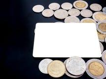 Carte vierge avec un bon nombre de pièces de monnaie sur le fond noir Photographie stock libre de droits