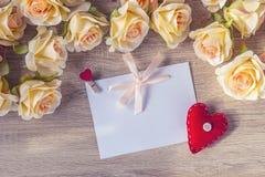 Carte vierge blanche avec un ruban rose, un coeur rouge et des roses o de pêche Photos libres de droits