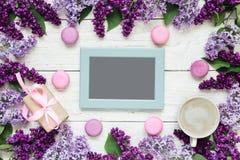 Carte vierge de photo dans le cadre fait de fleurs lilas avec la tasse, le boîte-cadeau et les macarons de café au-dessus de la t Images stock