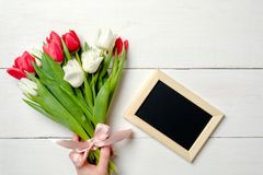 Carte vierge pour l'invitation ou la félicitation avec le groupe de fleurs de tulipes sur la table en bois blanche Maquette de ba image libre de droits