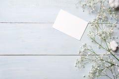 Carte vierge pour l'invitation ou la félicitation, petit boîte-cadeau, groupe de fleurs de gypsophila sur la table en bois bleu-c image stock
