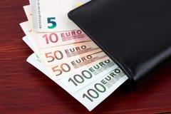 Carteira com dinheiro europeu em um fundo de madeira Fotografia de Stock