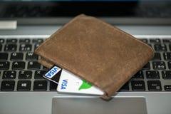 Carteira com os cartões de crédito do visto no portátil Foto de Stock