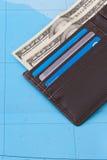 Carteira com os cartões do dinheiro e de crédito dos dólares no fundo do mapa Imagens de Stock Royalty Free